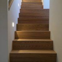 Iepen houten trap met ingebouwde leuning
